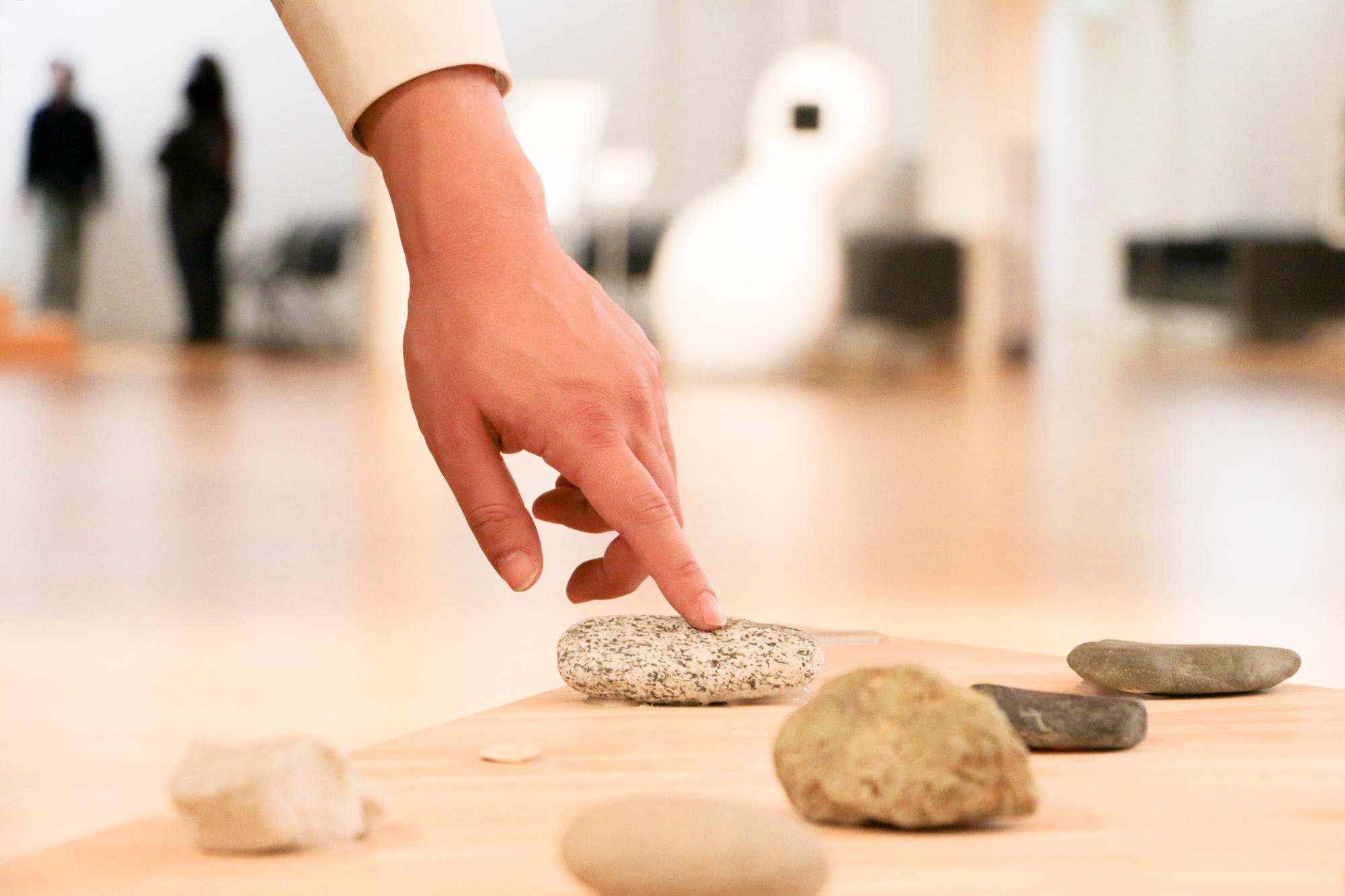 石に触れる手
