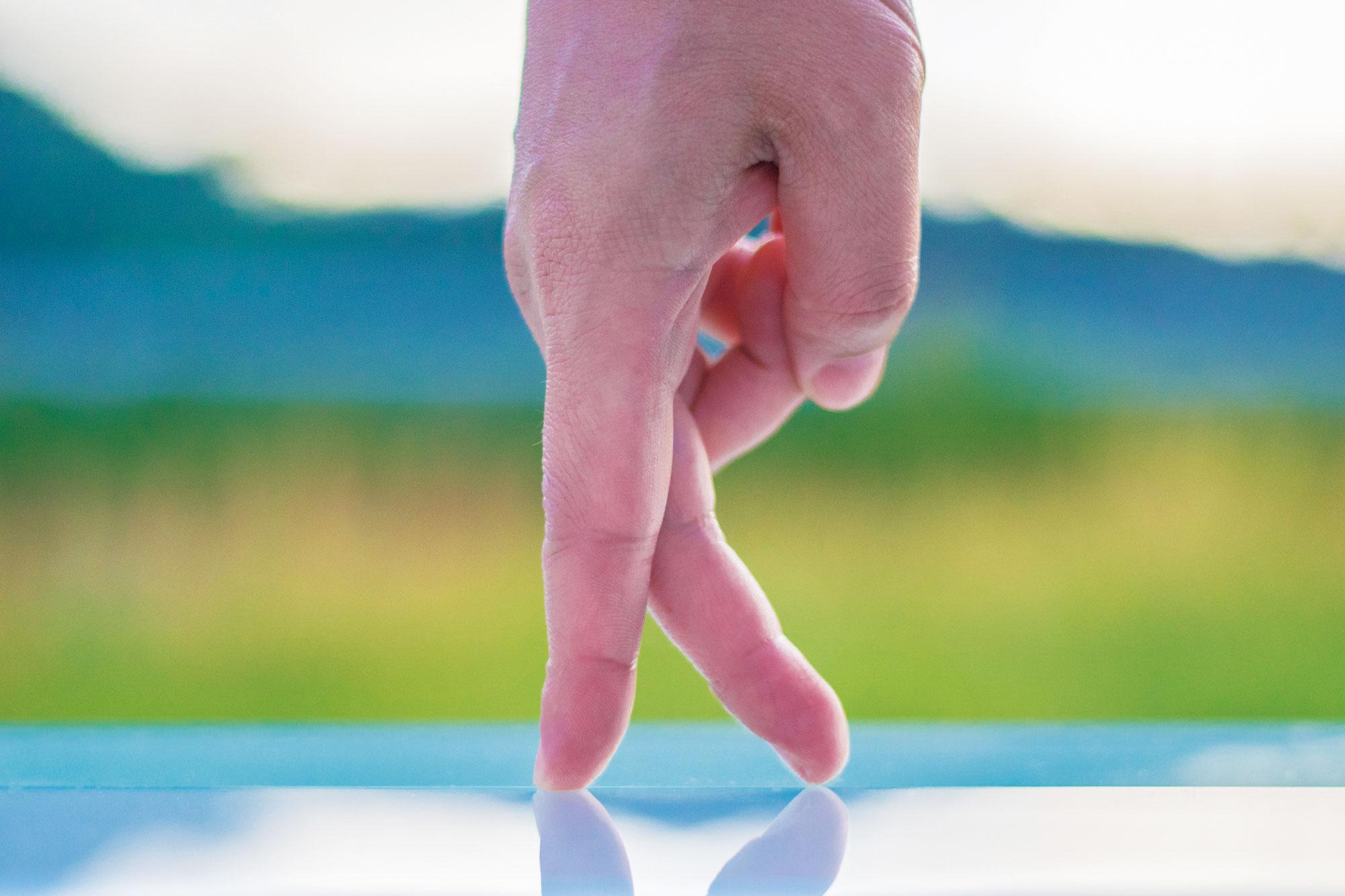 指が一本の線の上を歩くイメージの写真