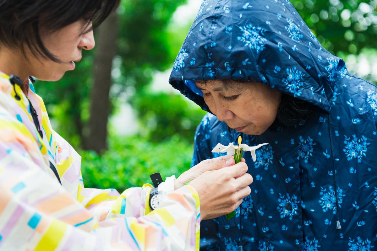 クチナシの花の香りをかぐ小倉さん