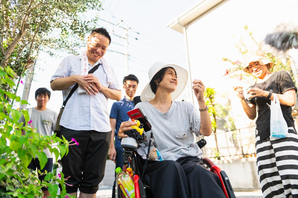車椅子から手を伸ばし植物にふれるのが好きな和久井さん