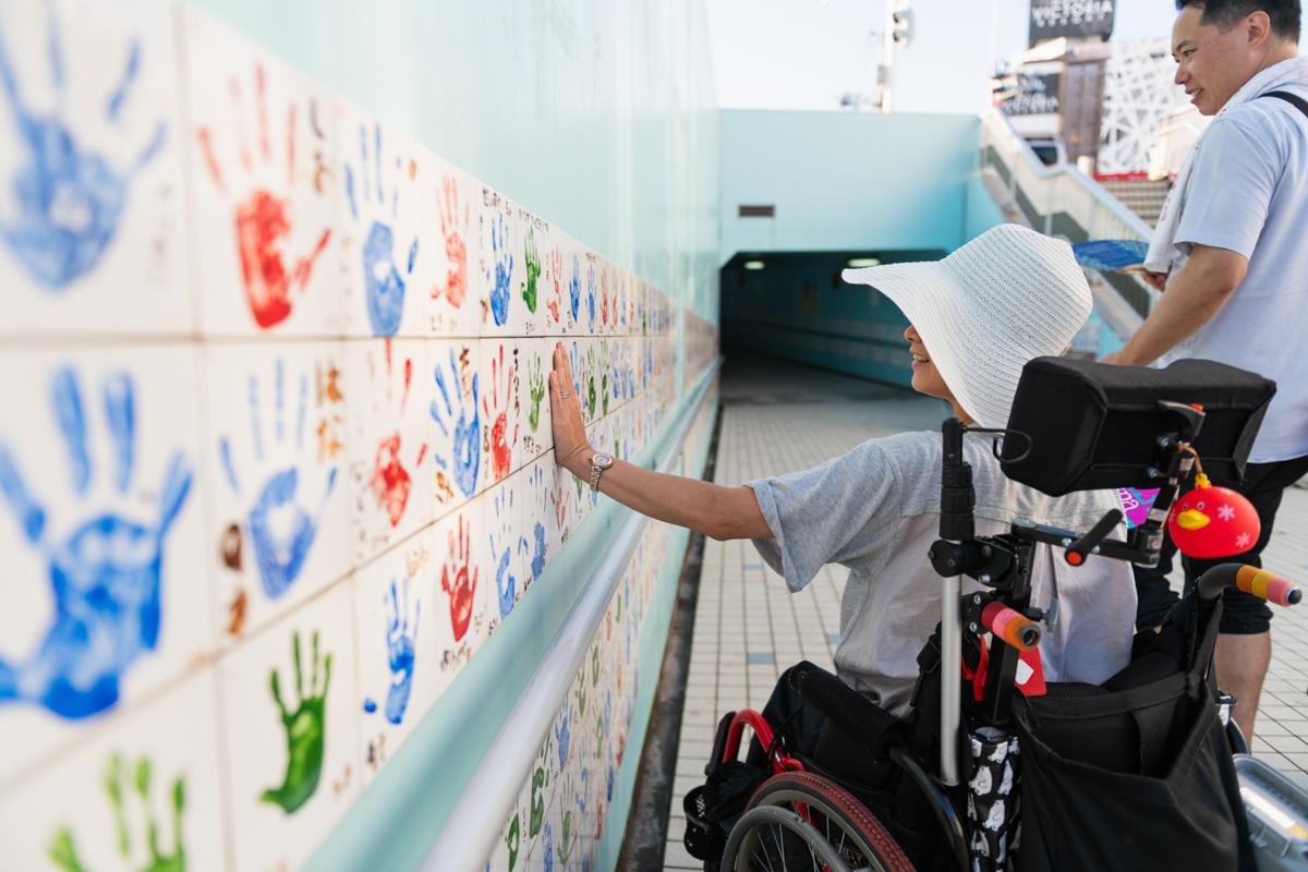 地下道の壁に飾られている小学生たちの手形に手をあてる和久井さん