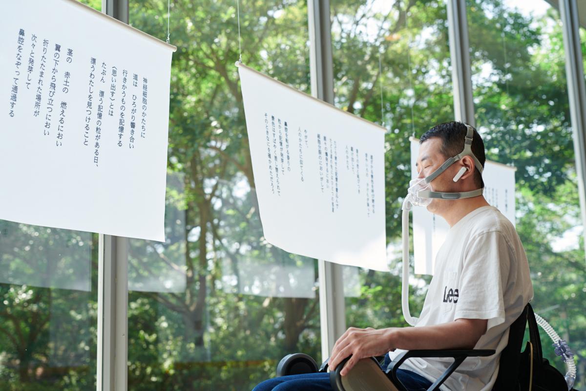 特別展示された蜂飼耳さんの詩の前に佇むインクルーシブデザインのファシリテーター・鎌倉丘星さん