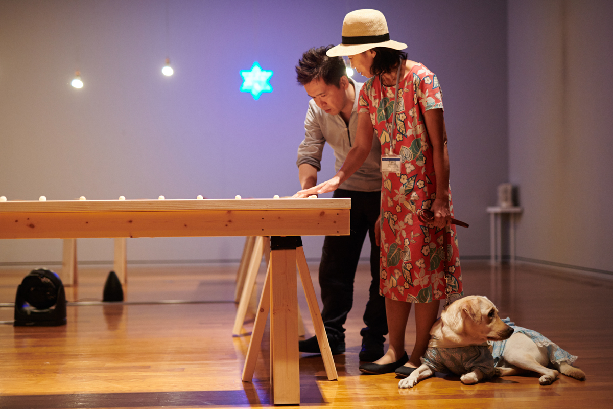 盲導犬ユーザーの小倉さんと聴覚障害をもつ西岡さんが作品を体験する様子
