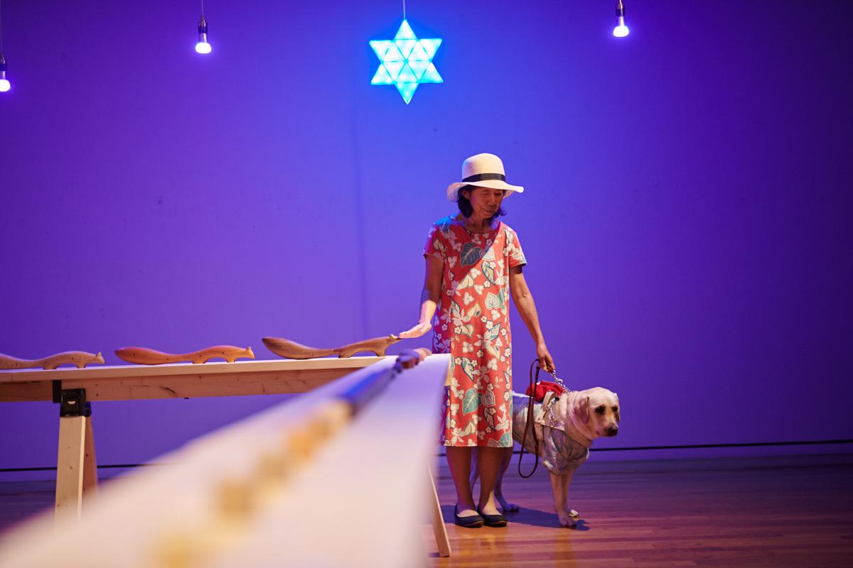 作品「うつしおみ」を体験する盲導犬ユーザーの小倉さんと盲導犬のブリス