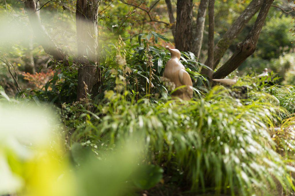 木々の中に顔をのぞかせる鳥の木彫